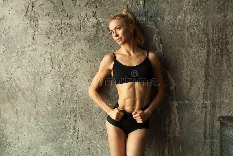 Femme de blondie de forme physique se tenant près du mur photos stock