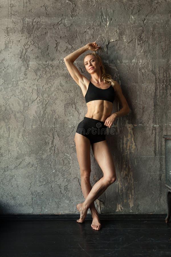 Femme de blondie de forme physique se tenant près du mur et de la fenêtre photo libre de droits