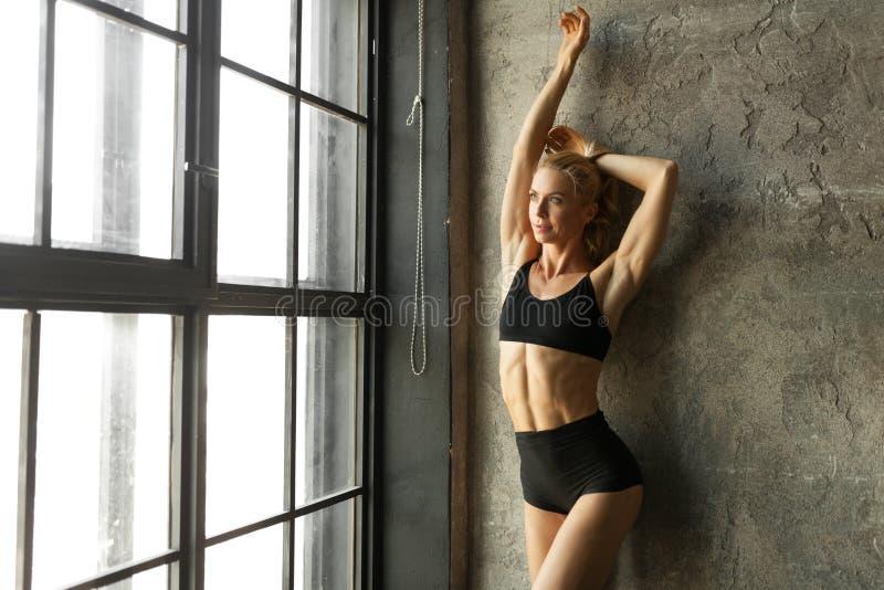 Femme de blondie de forme physique se tenant près du mur et de la fenêtre image libre de droits