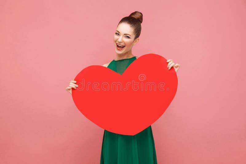 Femme de bonheur tenant le grand coeur rouge, sourire toothy photos stock