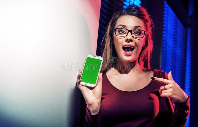 Femme de brune à l'aide de son smartphone photo stock