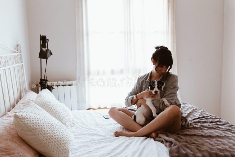Femme de brune ?treignant son chiot doux de Labrador dans la chambre ? coucher image libre de droits