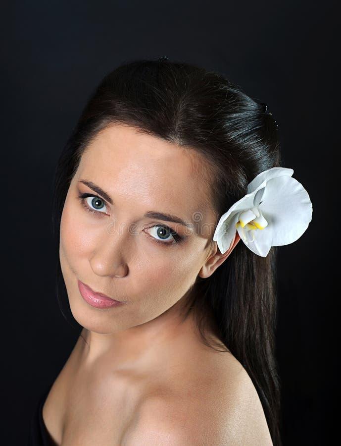 Femme de brune avec l'orchidée blanche dans les cheveux photos stock