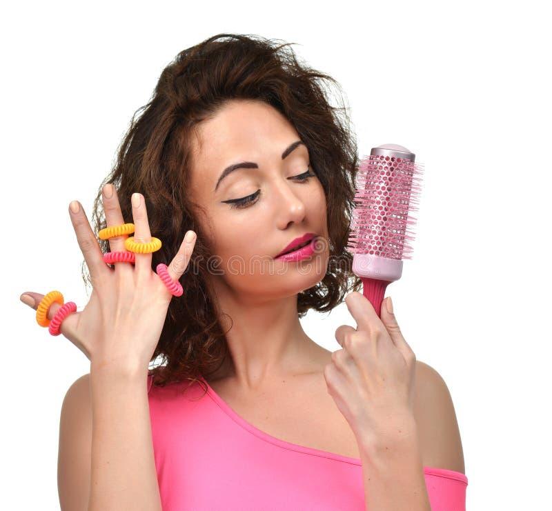 Femme de brune avec la grande brosse de cheveux rose et scrunchy regardant le coin photographie stock