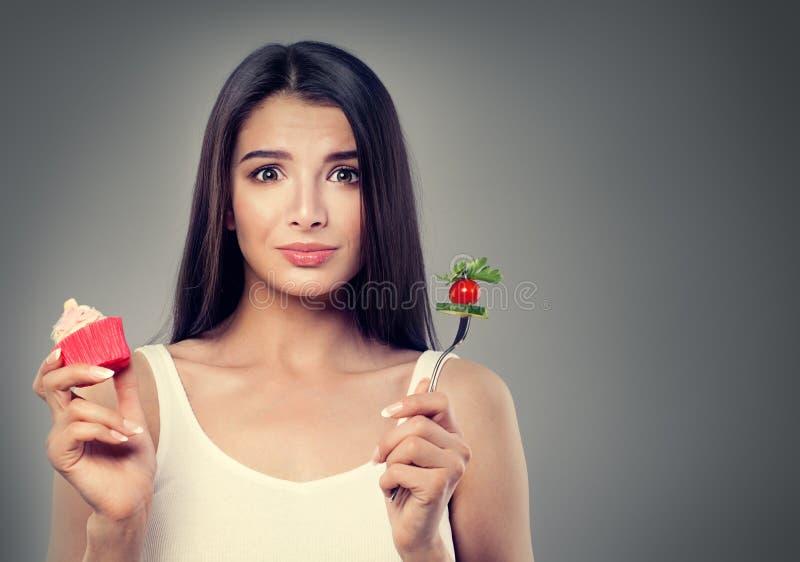 Femme de brune avec la nourriture saine et malsaine photographie stock