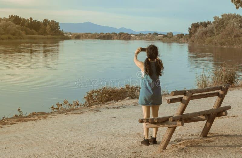 Femme de brune avec le cowboy bleu photographiant une rivière avec un mobile images stock
