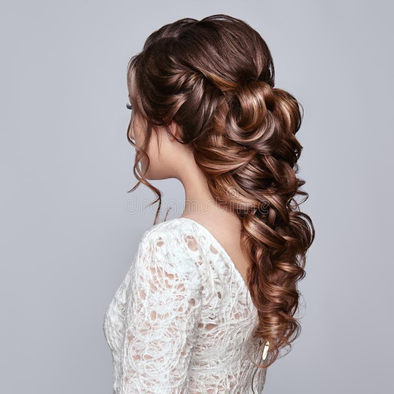 Femme de brune avec de longs et brillants cheveux bouclés photographie stock