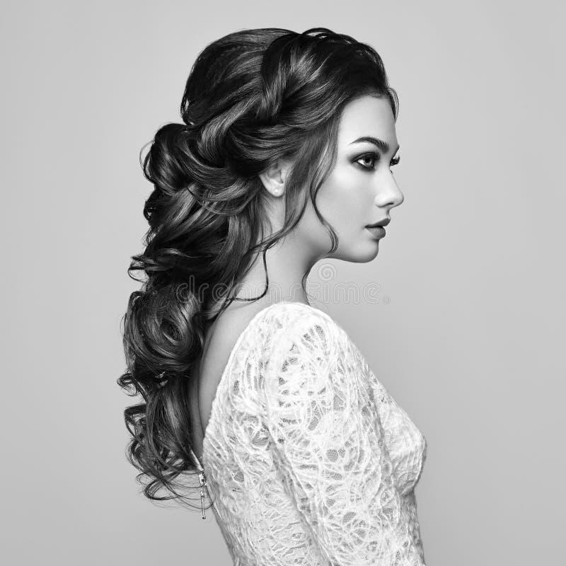 Femme de brune avec de longs et brillants cheveux bouclés photo stock