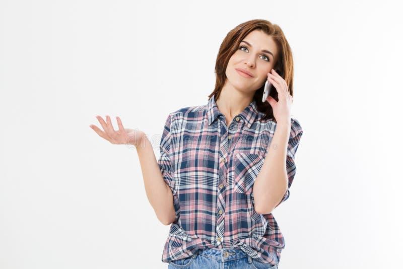 Femme de brune parlant sur le smartphone au-dessus du fond d'isolement se dirigeant avec des doigts sur l'espace de copie, signe  images stock