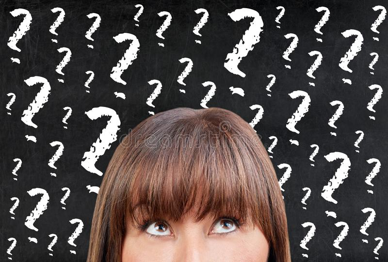 Femme de brune pensant contre des points d'interrogation de tableau de tableau noir photographie stock libre de droits