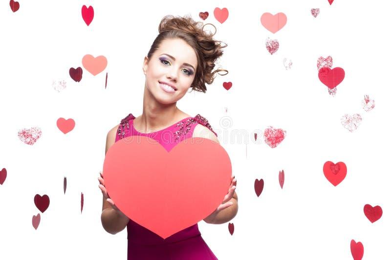Femme de brune retenant le grand coeur de papier rouge image libre de droits