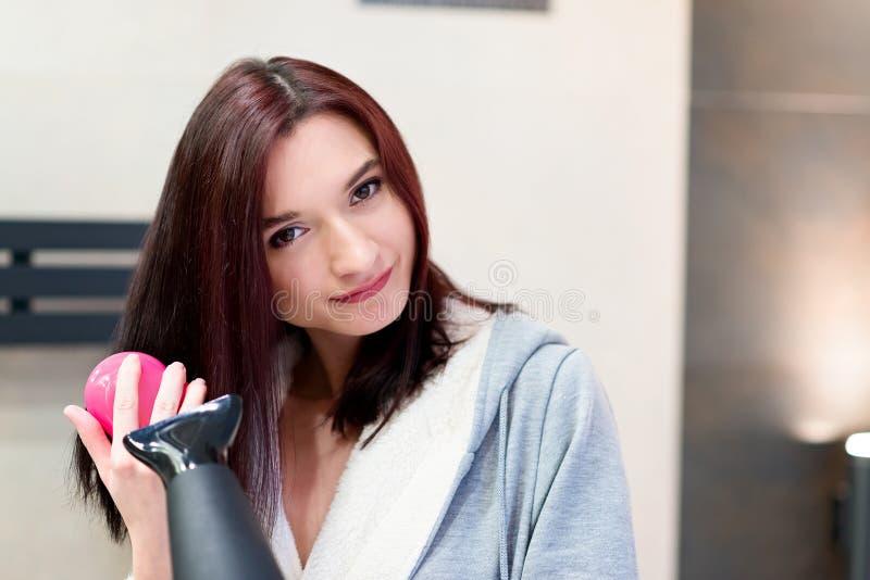 Femme de brune se brossant et séchant les cheveux photo libre de droits