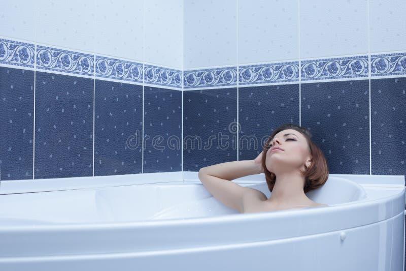 Femme de brune se situant dans le bain photos libres de droits