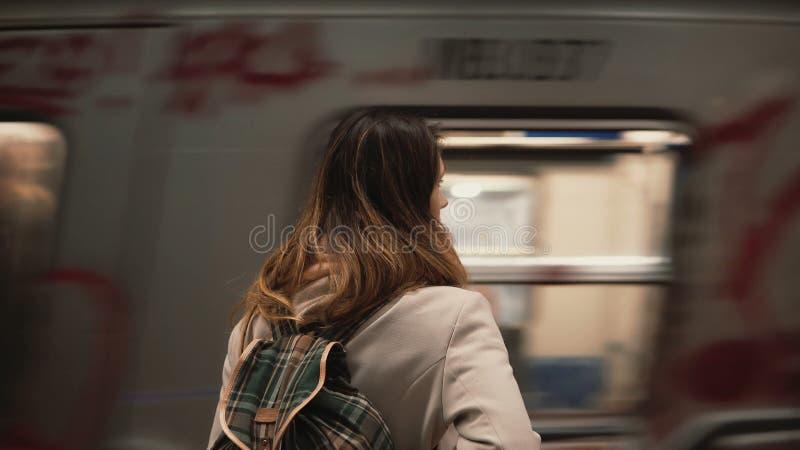 Femme de brune se tenant sur la gare ferroviaire et attendant son train La fille dedans sous terre à la soirée regarde sur les tr clips vidéos