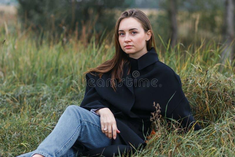 Femme de brune se trouvant sur l'herbe vert-foncé d'automne Style occasionnel de mode image stock