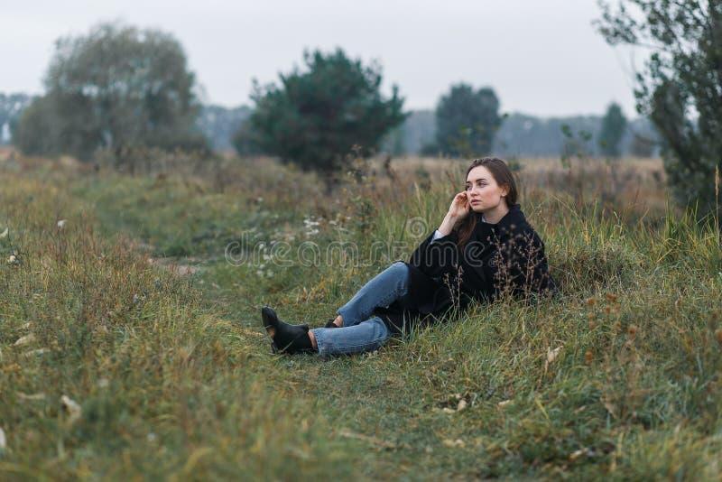 Femme de brune se trouvant sur l'herbe vert-foncé d'automne Style occasionnel de mode photo libre de droits