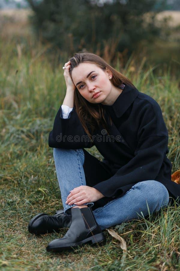 Femme de brune se trouvant sur l'herbe vert-foncé d'automne Style occasionnel de mode image libre de droits