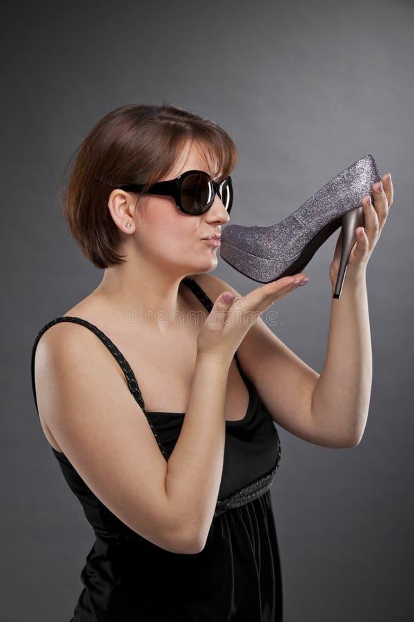 Femme de Brunette avec des lunettes de soleil embrassant une chaussure images stock