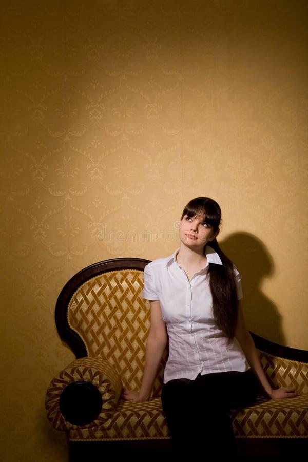 Femme de brunette de jeune femme s'asseyant sur le sofa photo stock