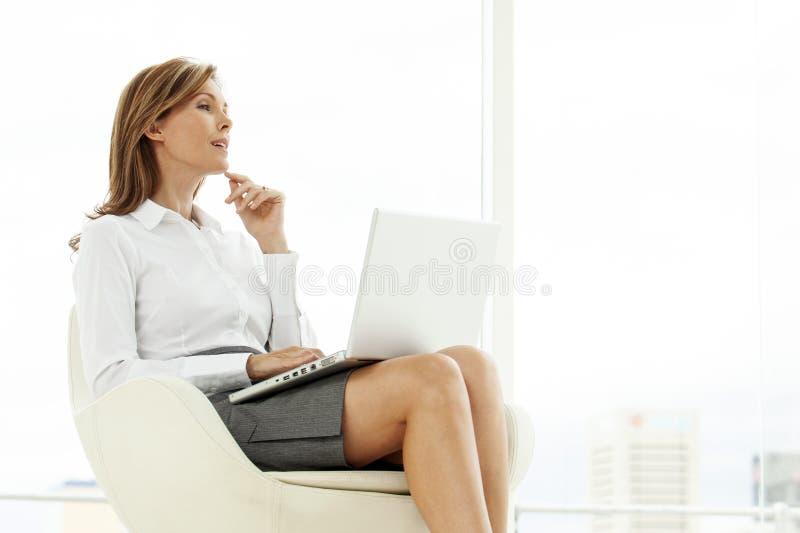 Femme de cadre d'entreprise à l'aide de l'ordinateur portable dans l'emplacement contemporain photos libres de droits