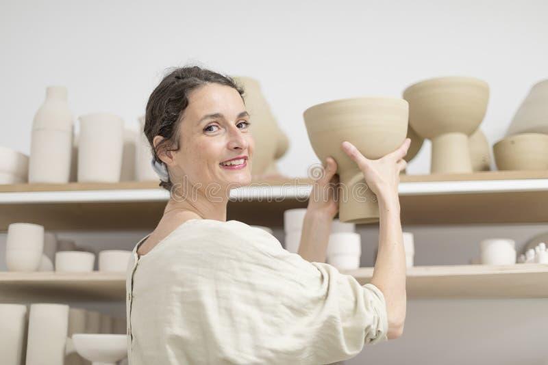Femme de Ceramist tenant un potier dans son studio image stock
