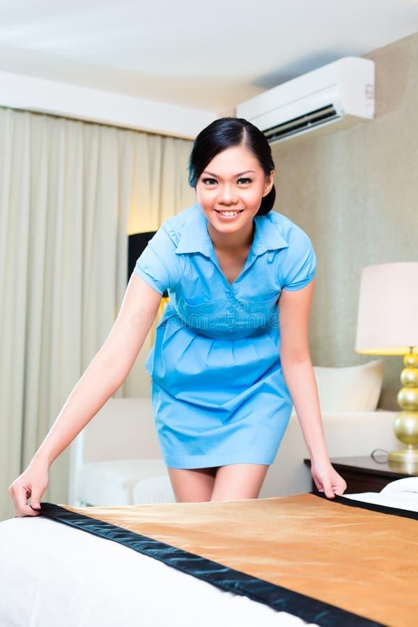 Femme de chambre faisant le lit dans l'hôtel asiatique image libre de droits
