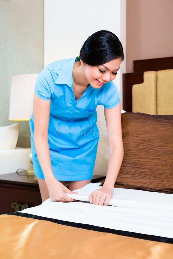 Femme de chambre faisant le lit dans la chambre d'hôtel images libres de droits