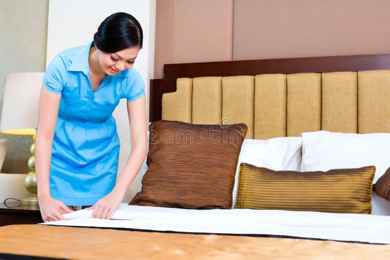 Femme de chambre faisant le lit dans la chambre d'hôtel photo stock