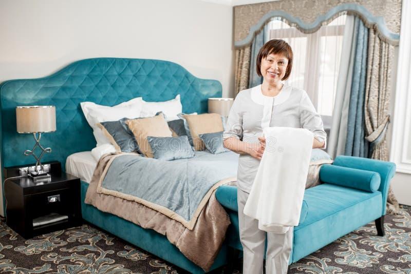 Femme de chambre supérieure à la chambre d'hôtel photographie stock libre de droits