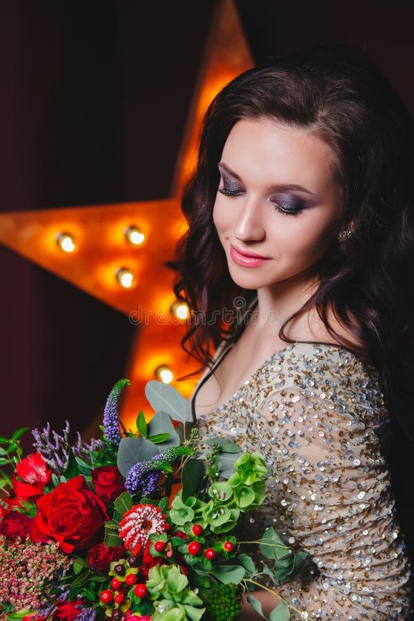 Femme de chanteur dans la robe de scintillement avec l'étoile de Broadway sur le fond Coiffure bouclée, maquillage parfait Fleurs photographie stock