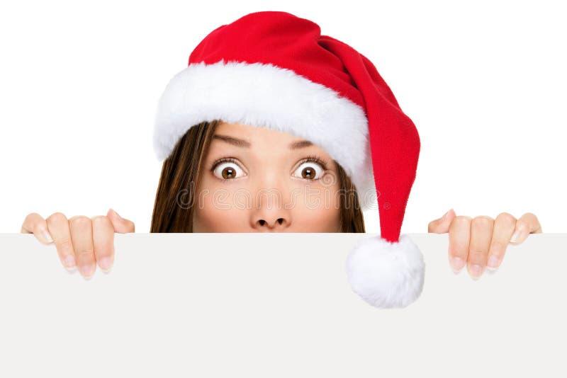Femme de chapeau de Santa affichant le signe de Noël photographie stock libre de droits