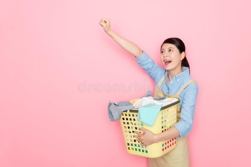 Femme de charge assez féminine tenant le panier d'habillement photographie stock