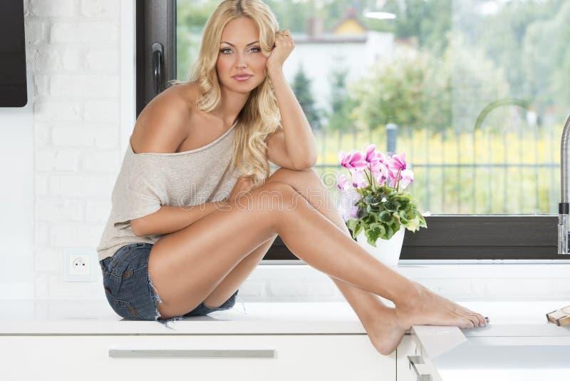 Femme de charge blonde sensuelle dans la cuisine photographie stock libre de droits