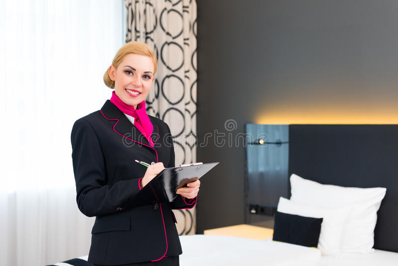 Femme de charge vérifiant la chambre d'hôtel image libre de droits