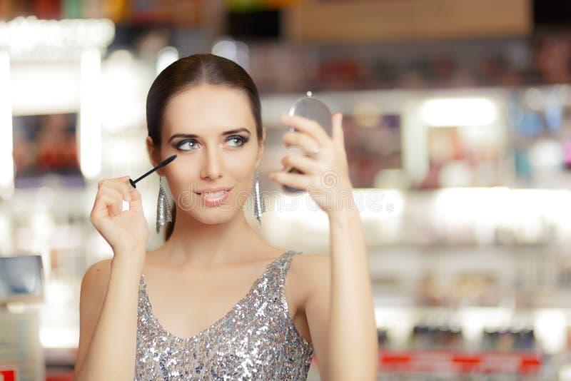 Femme de charme avec le miroir de mascara et de maquillage photos stock
