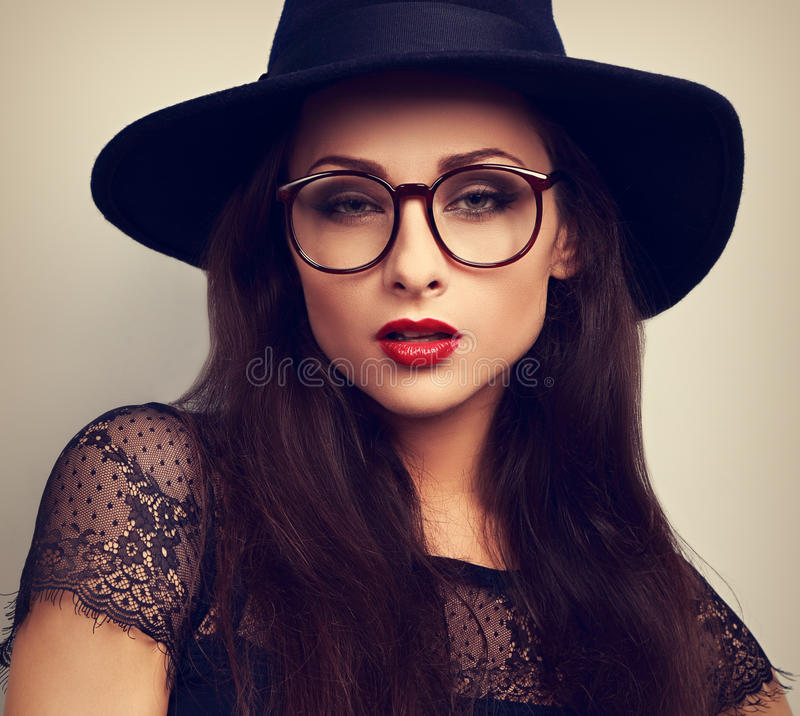 Femme de charme de maquillage dans le regard de lunettes de mode et de chapeau noir image libre de droits