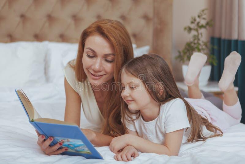 Femme de charme lisant un livre ? sa petite fille photos stock