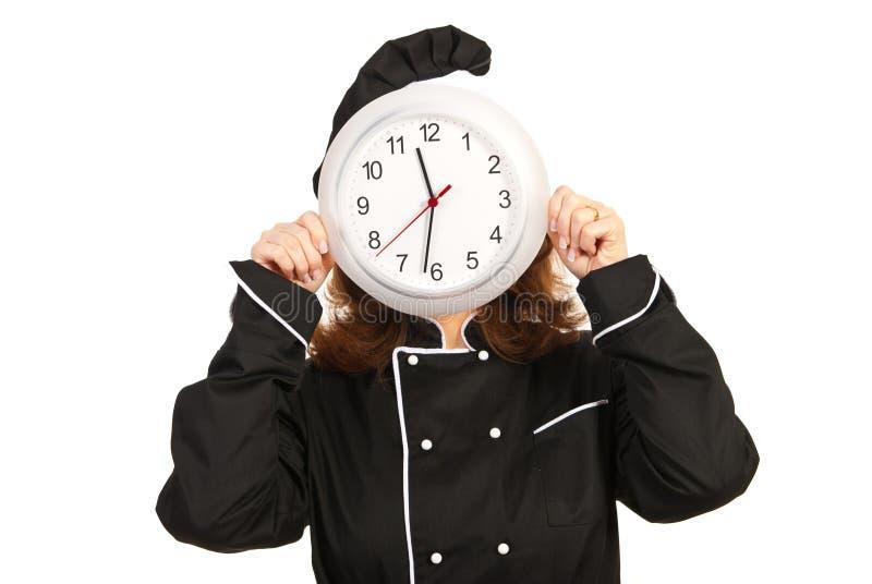 Femme de chef derrière l'horloge images stock