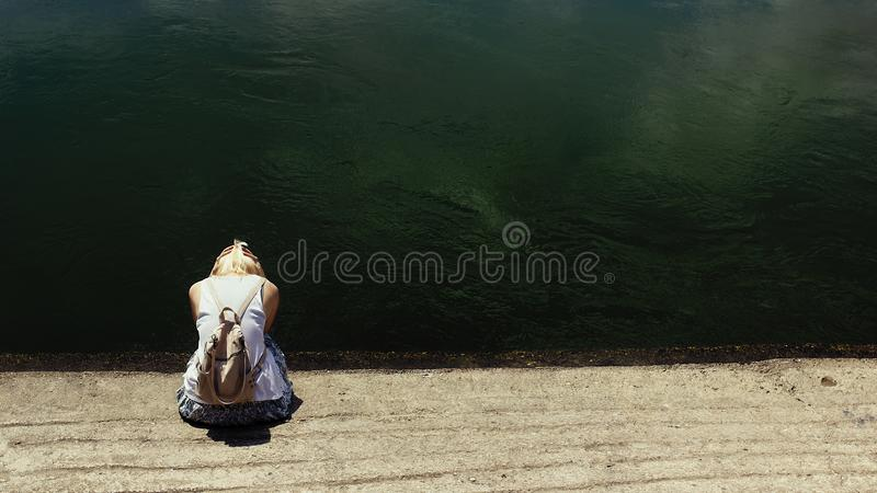 Femme de cheveux blonds s'asseyant par l'eau de rivière foncée, triste photos libres de droits
