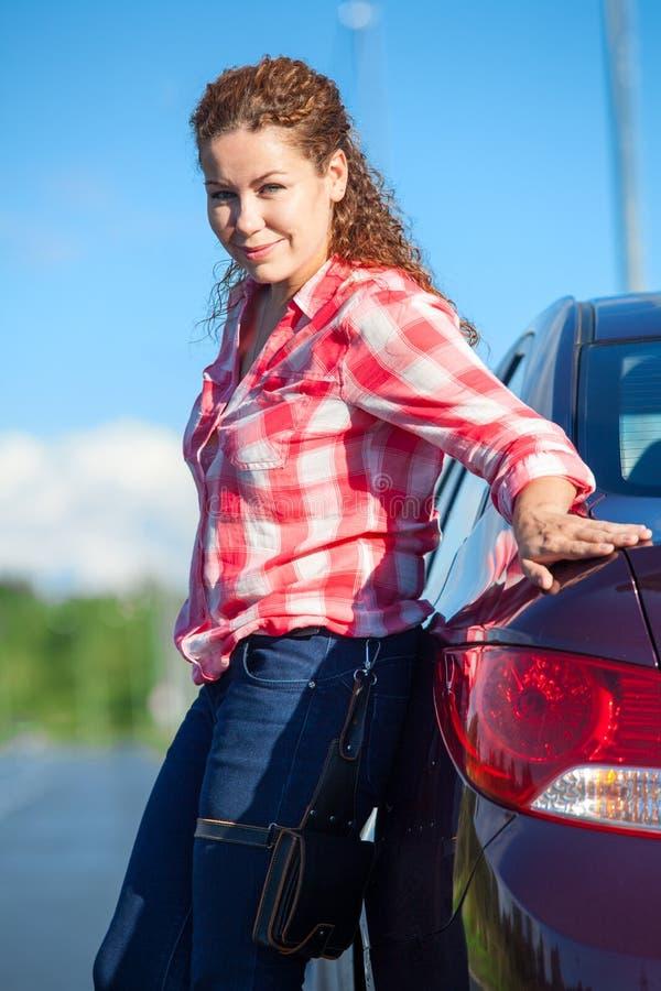 Femme de cheveux bouclés dans la chemise rouge et blanche se penchant sa voiture tout en tenant le côté de route photos libres de droits