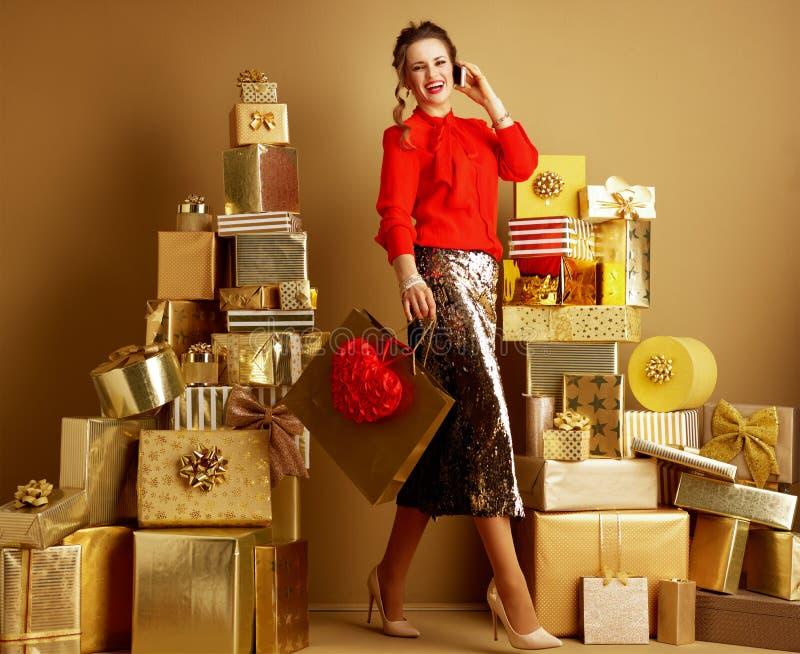 Femme de client avec le sac à provisions et coeur rouge utilisant un téléphone portable photo stock