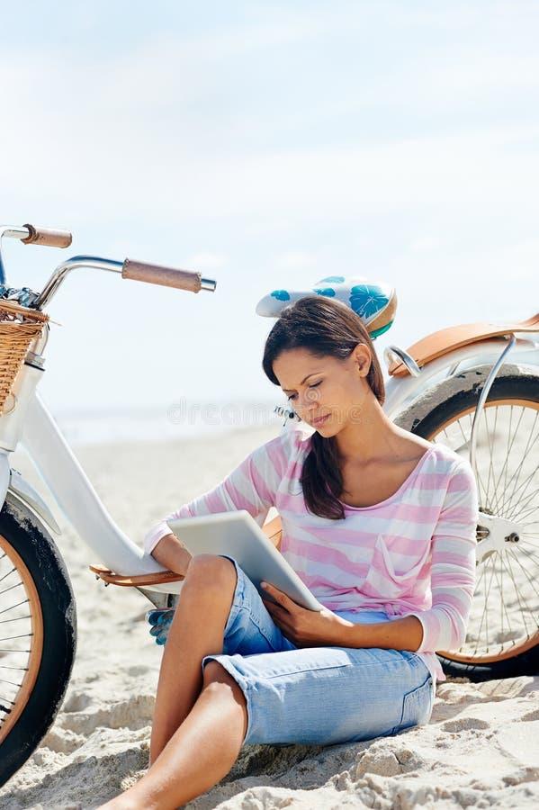 Femme de comprimé de bicyclette de plage photo stock