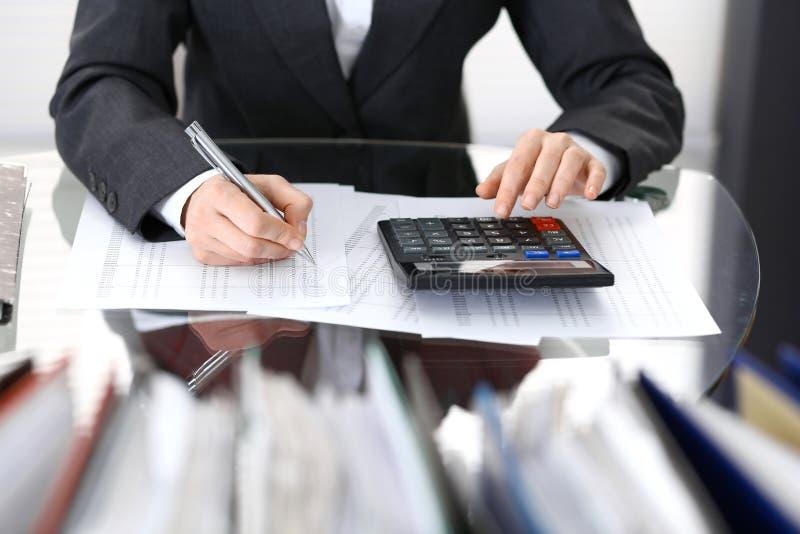 Femme de comptable ou inspecteur financier rédigeant le rapport, calculant ou vérifiant l'équilibre, plan rapproché Portrai d'aff photo stock