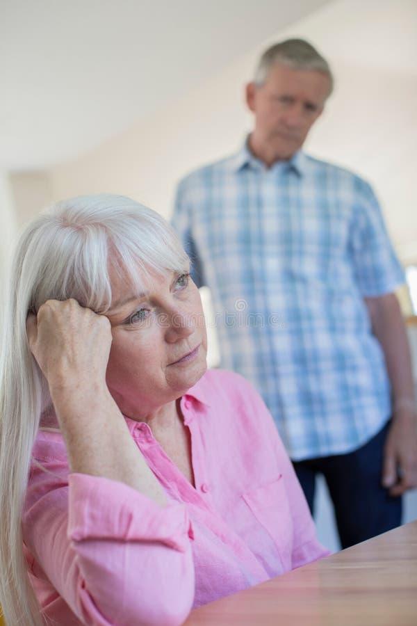 Femme de consolation mûre d'homme avec la dépression à la maison photographie stock libre de droits