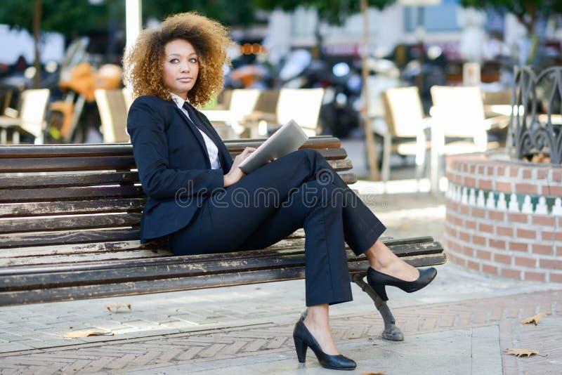 Femme de couleur à l'aide de la tablette en ville images libres de droits