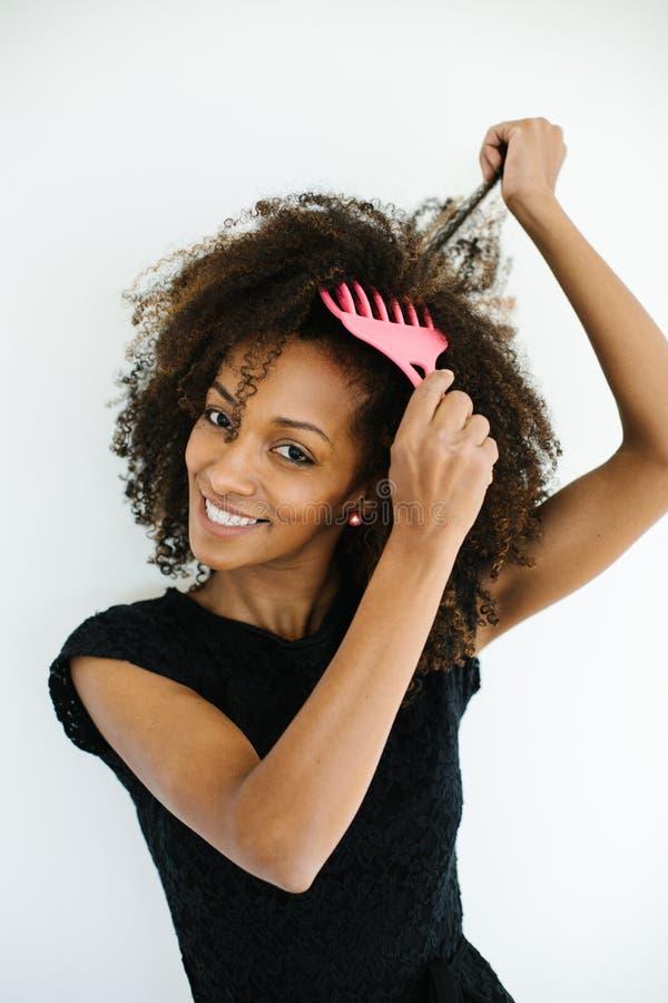 Femme de couleur à l'aide du peigne Afro de cheveux photographie stock libre de droits