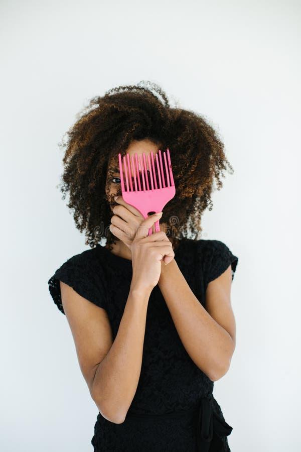 Femme de couleur à l'aide du peigne Afro de cheveux images stock