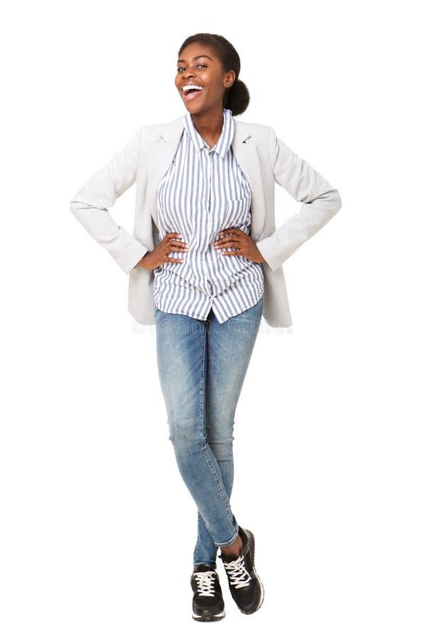 Femme de couleur attirante de plein corps jeune dans le blazer souriant sur le fond blanc d'isolement images stock