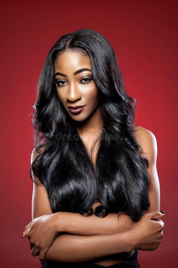 Femme de couleur avec de longs cheveux brillants luxueux photos stock