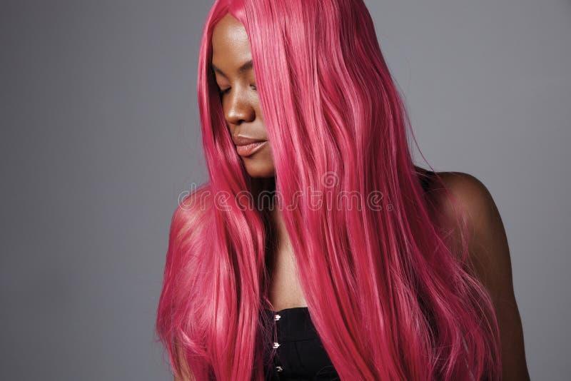 Femme de couleur avec de longs cheveux roses droits brillants images libres de droits